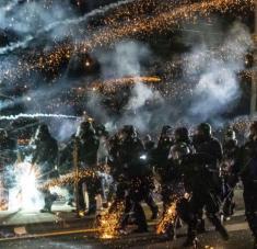 Los agentes del estado de Oregón, EE.UU., avanzan a través de gas lacrimógeno mientras dispersan una protesta antirracista, 5 de septiembre de 2020. Foto: AFP.
